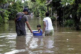 Une famille se déplace dans une rue inondée de Taggerang près de Jakarta en Indonésie le 02 janvier