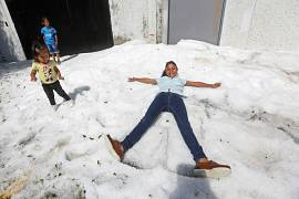 Residents play on top of ice after a heavy storm of rain and hail which affected some areas of the city in Guadalajara