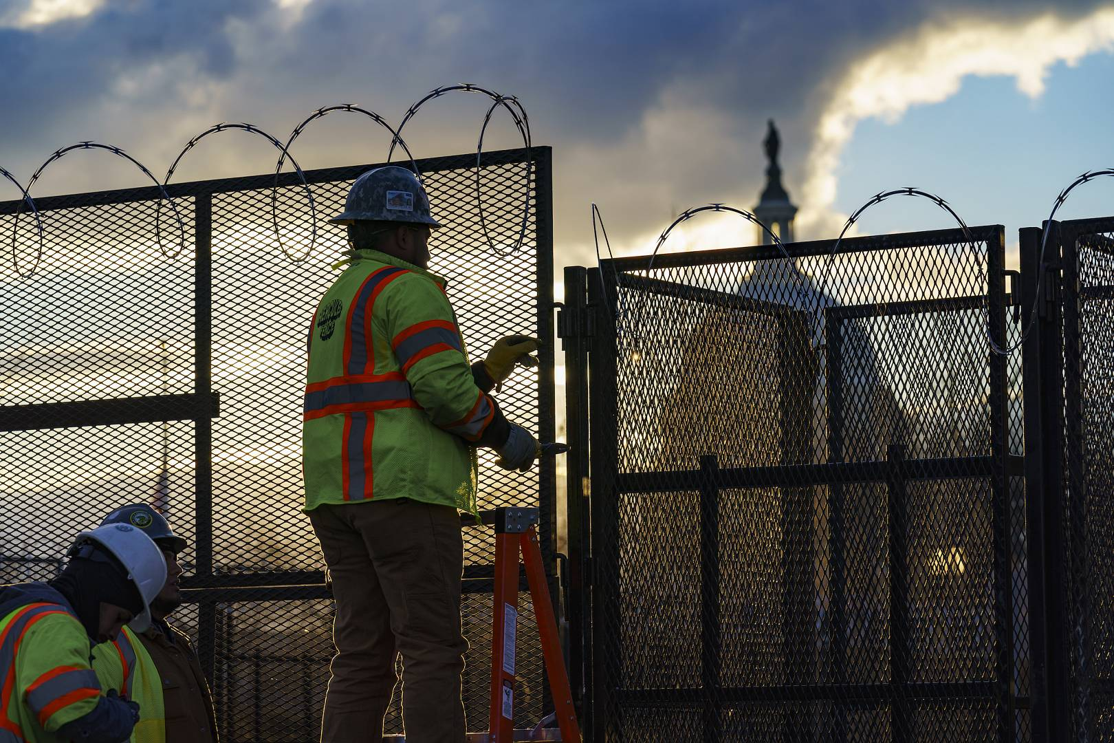 Workers install razor wire atop of fencing around the U.S. Capitol perimeter at sunset, in Washington. January 18, 2021
