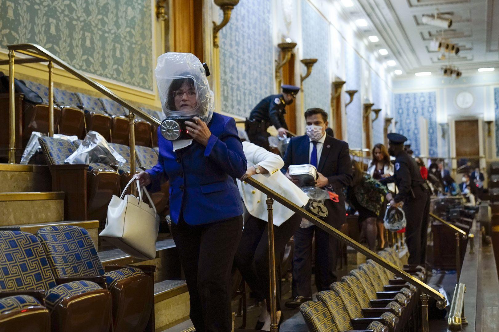 Orang-orang berlindung di galeri House saat pengunjuk rasa hendak masuk ke House Chamber di US Capitol di Washington, AS. 6 Januari 2021