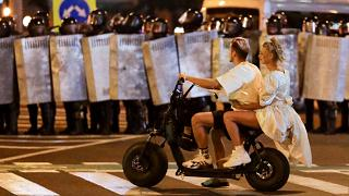 A rendőrsorfal előtt motorozik egy fiatal pár Minszkben