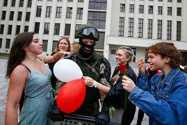 Women greet a soldier guarding the Belarusian government building in Minsk, Belarus. August 14, 2020
