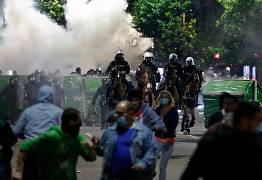 Sebian police officers disperse protesters in front of Serbian parliament building in Belgrade, Serbia, July 8, 2020