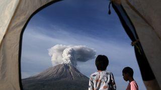 Indonesian children watch Mount Sinabung erupting in Karo, North Sumatra, Indonesia. March 11, 2021