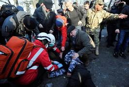 aramedics help an injured activist of the far right movement following clashes during a protest against land sale reform in front of the Ukrainian Parliament in Kiev on 17/12