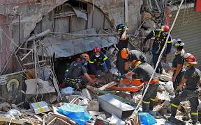 Members of the Lebanese civil defence use a dog to search for victims and survivors under the rubble of a building in the Gemayzeh neighbourhood on August 6, 2020