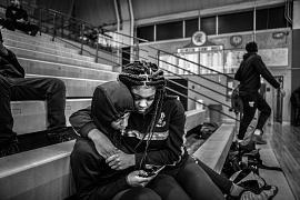 Jaguars junior Dion Brown sits with his girlfriend Lakenya Thomas as they watch a junior varsity game in a nearly empty gym. 24 February 2020