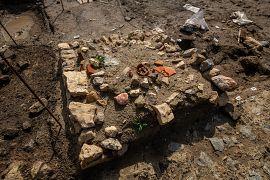 Petit monument funéraire installé sur une tombe avec au centre le sommet de l'amphore utilisée comme conduit à libation et intégrée à la maçonnerie.