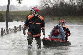 A resident of La Faute sur Mer, on the Atlantic coast in south western France is evacuated by firefighters as a result of a storm, Monday, March 1, 2010.
