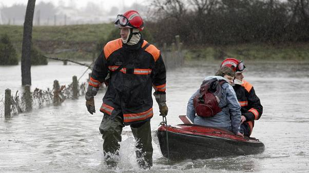 A resident of La Faute sur Mer, on the Atlantic coast in south western France is evacuated by firefighters as a result of a storm.