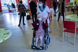 La belga Josepha Delmotte, 102 anni, al centro, saluta dopo aver ricevuto la vaccinazione COVID-19 presso la casa di cura La Bonne Maison de Bouzanton a Mons, Belgio, lunedì 2