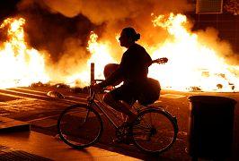 Un hombre pasa en bicicleta junto a un incendio en Barcelona, España, el 15 de octubre de 2019.