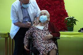 La belga Josepha Delmotte, 102 anni, al centro, saluta dopo aver ricevuto la vaccinazione COVID-19 presso la casa di cura La Bonne Maison de Bouzanton a Mons, Belgio