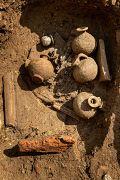 Tombe à crémation constituée d'un amas d'ossements humains brûlés surmonté de cruches en céramique et d'un petit balsamaire (vase à parfum) en verre.