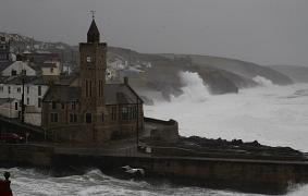Powerful waves break on the shoreline around the small port of Porthleven, south west England.