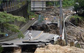 A man walks on heavily damaged road following a heavy rain in Kumamura, Kumamoto prefecture, southern Japan. 6 July 2020