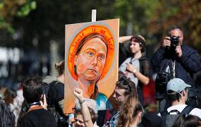 A man holds a placard depicting Swedish climate activist Greta Thunberg as people take part in the Fridays for Future climate change action protest in Paris, France