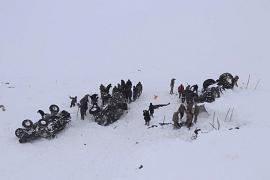 Emergency service members dig in the snow around at least three overturned vehicles, near the town of Bahcesehir, in Van province, eastern Turkey.