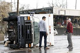 A overturned truck sits in a street in an area damaged by storms.