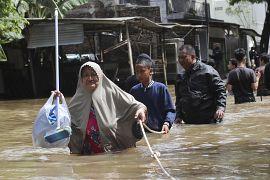 Des habitants se déplacent en tenant une corde dans une rue inondée de Taggerang près de Jakarta en Indonésie le 02 janvier