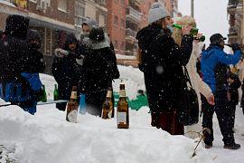 La gente mantiene sus cerveza frías en la nieve durante la nevada en el centro de Madrid, España, el 9 de enero de 2021.
