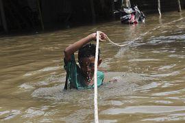 Un enfant se déplace en tenant une corde dans une rue inondée de Tanggerang près de Jakkarta, le 02 janvier