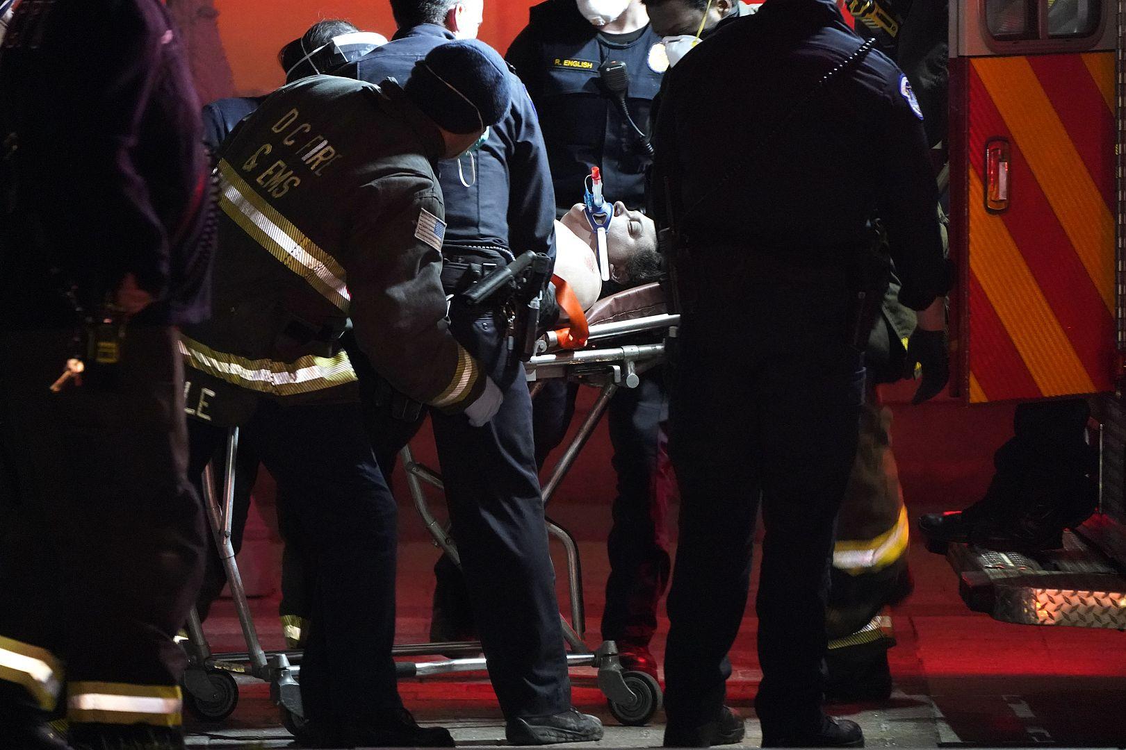 Seseorang dengan tandu ditempatkan di ambulans di luar US Capitol di Washington, AS. 6 Januari 2021