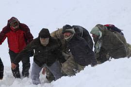 Emergency service members carry a victim of an avalanche, near the town of Bahcesaray, in Van province, eastern Turkey.