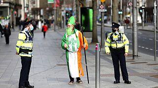 Un hombre disfrazado de San Patricio habla con la policía