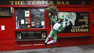 Egy férfi Szent Patrik napi öltözékben Dublin legendás pubja, a Temple Bar előtt