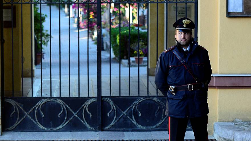 Italian Carabinieri police officer patrols outside the cemetery in Corlene