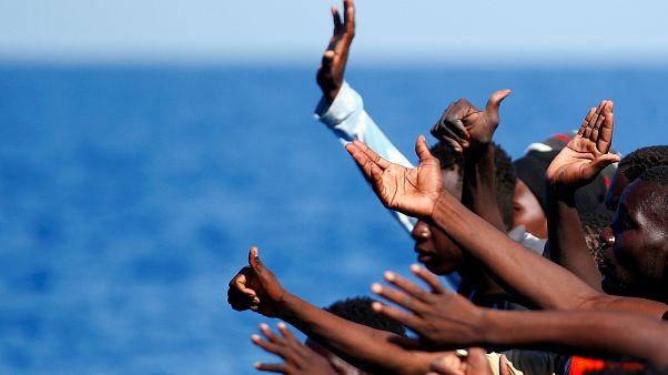 Migrants gesture as before they are rescued by SOS Mediterranee organisatio