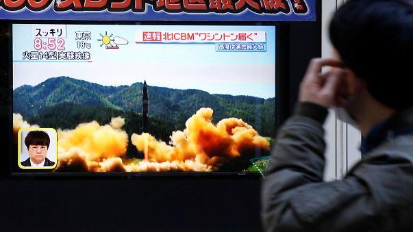 Egy férfi nézi a rakétakilövésről szóló hírt a tévében Tokióban