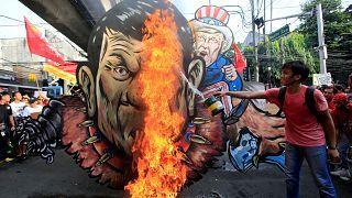 An activist pours gasoline as an effigy of President Rodrigo Duterte