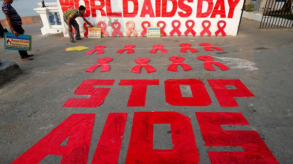 A man places a placard as he prepares a message during an HIV/AIDS awarenes