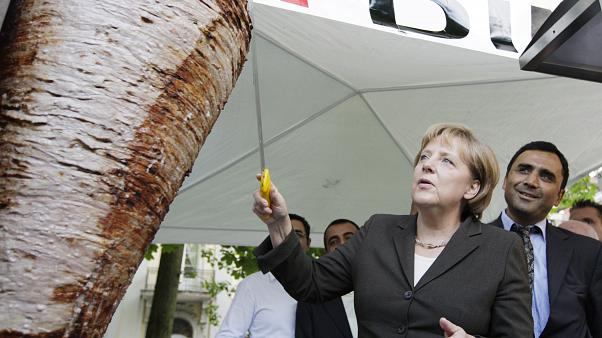 German Chancellor Angela Merkel cuts a piece from a kebab meat loaf