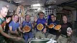 Astronauts aboard the International Space Station show off their pizzas.
