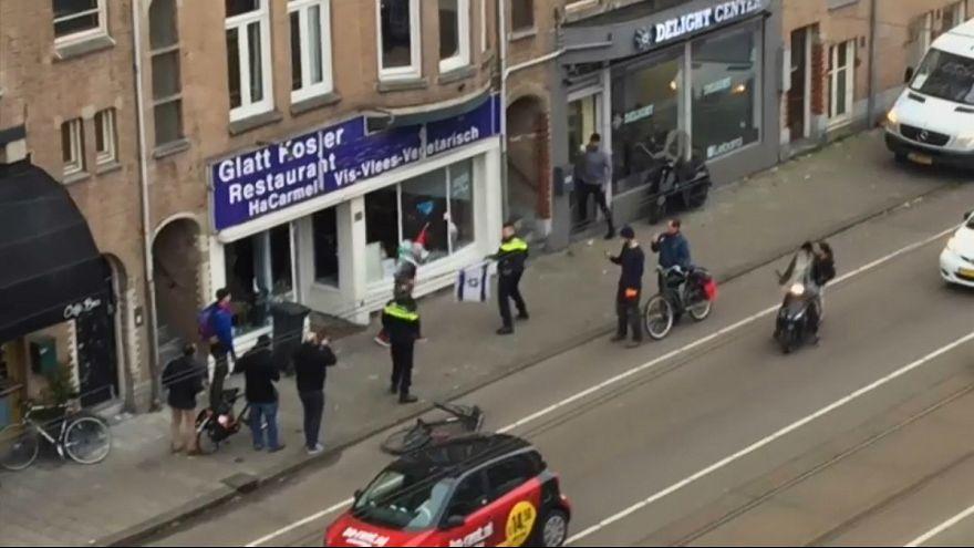 مردی با پرچم فلسطین در دست شیشههای رستوران یهودیان در آمستردام را شکست