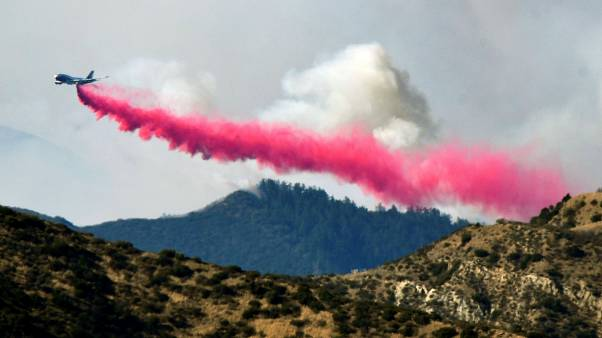 An aircraft drops fire retardant on a wildfire in Filmore, California