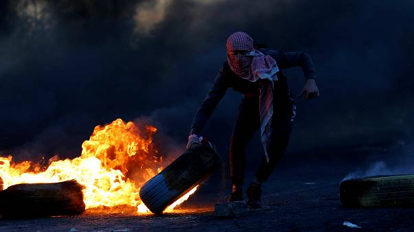 Palestinian moves a tire during clashes with Israeli troops at a protest