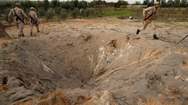 مقاتلون من حركة حماس يفحصون موقع غارة إسرائيلية شمال قطاع غزة
