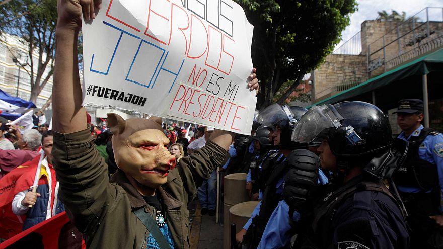 Ein Unterstützer des Herausforderers Nasralla steht der Polizei gegenüber