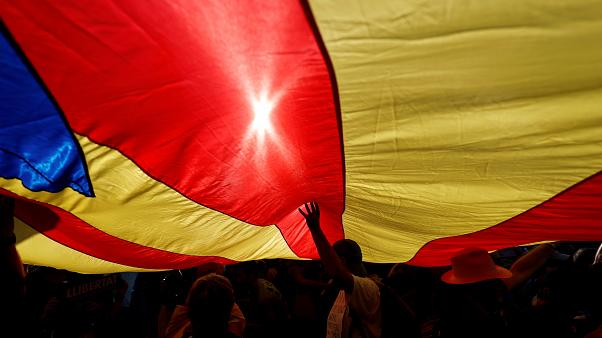 People stand under a giant separatist Catalonian flag during a demonstratio