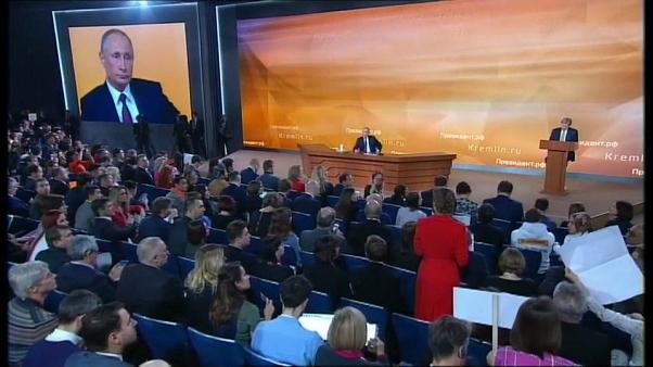 La periodista Ksenia Sobchak, de pie con un vestido rojo, pregunta a Putin