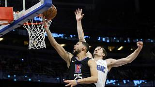 Austin Rivers, dos Clippers, impõe-se no cesto a Mario Hezonj, dos Magic