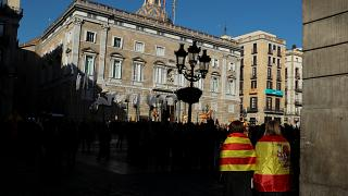 Woman wear Spanish and Catalan flags as they gather at Sant Jaume square