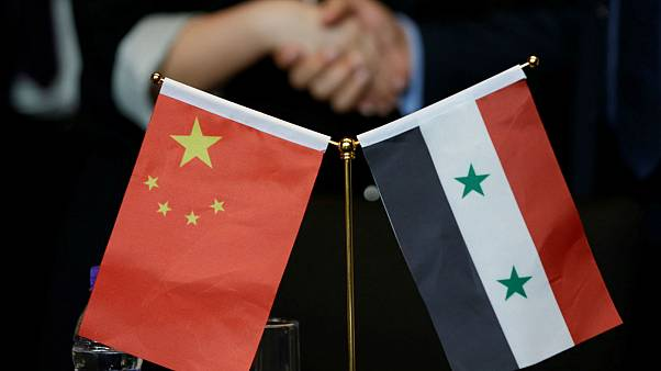 Chinese and Syrian businessmen shake hands behind their national flags