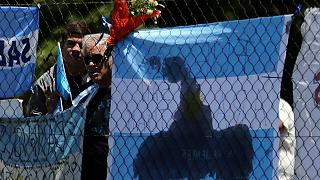 People stand next to a bouquet of flowers in support of missing submarine
