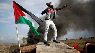 Egy palesztin tüntető csúzlival repít követ az izraeli katonák felé Gázában