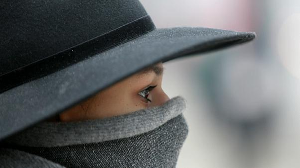 Woman walks with a covered face to protect herself from air pollution
